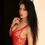 Sultry Alluring Vixen babe Erika G teases in a very skimpy red net dress that leaves little to the imagination