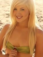 Blonde beach babe Ashlie is at the beach in a skimpy strapless shinny bikini