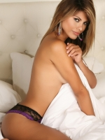 Alluring Vixen Claudia teases in just panties as she rolls around in bed topless